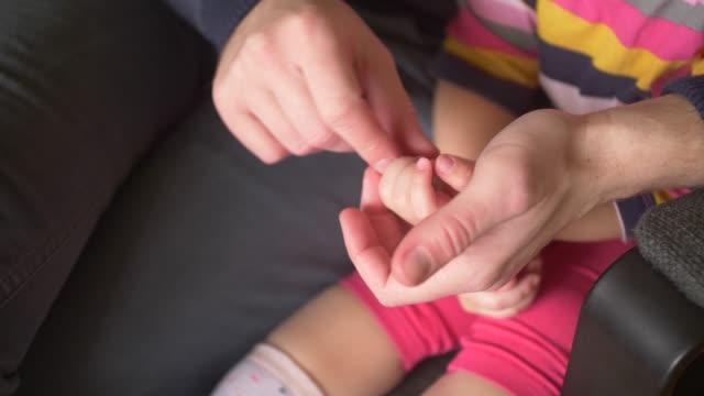fingerplay - father's hand passes over daughter's palm and fingers - fem objekt bildbanksvideor och videomaterial från bakom kulisserna