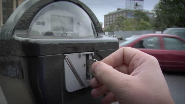 vídeos y material grabado en eventos de stock de cu fingers inserting quarter into coin slot on parking meter as traffic drives past / new york, new york, usa - máquina con ranura