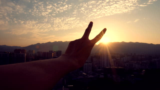 fingers making a peace sign at sunset - v sign stock videos & royalty-free footage