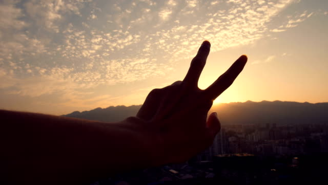 fingers making a peace sign at sunset - symbol stock videos & royalty-free footage