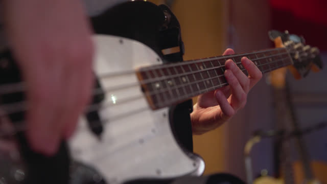 fingers move across an electric bass guitar fretboard - fretboard stock videos & royalty-free footage