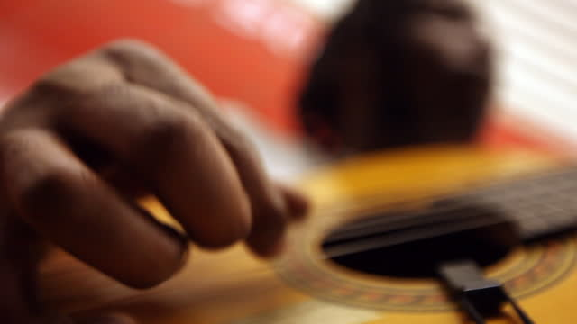 CU fingers of black man playing guitar while leaning against red wall in subway station