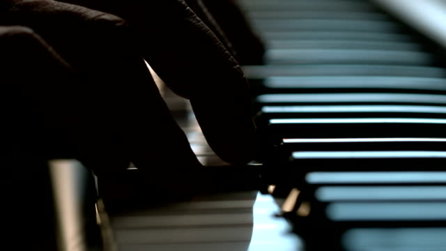 Fingers playing on the keys of a piano
