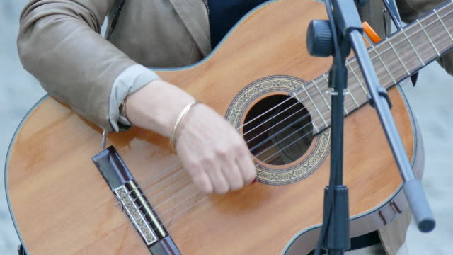 Fingers strumming on guitar strings