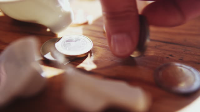 fingers taking coins from broken piggy bank. - currency symbol stock videos & royalty-free footage