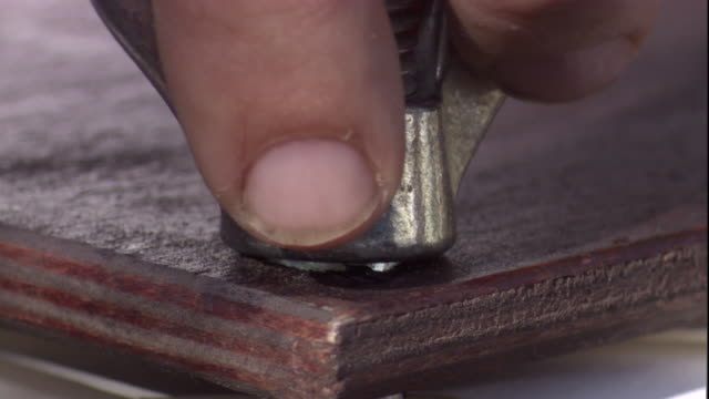 Fingers turn the wing nut on a specimen press. Available in HD.
