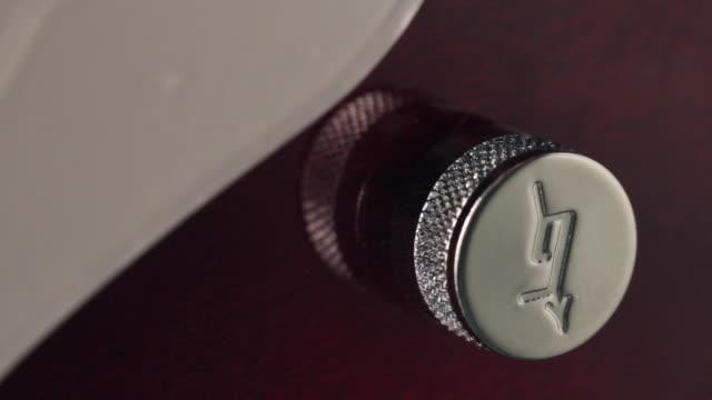 vídeos de stock e filmes b-roll de ecu fingers turning guitar volume knob / london, united kingdom - dedo humano