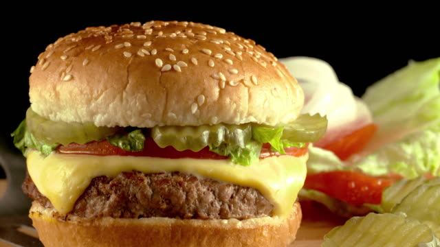 cu finished hamburger with cheese onion lettuce tomato and pickles placed on plate  - hamburger stock videos and b-roll footage