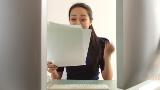 vídeos de stock, filmes e b-roll de alegria do trabalho do revestimento, jogando o papel no ar ao trabalhar em uma mesa.  mulher asiática bonita. - papel