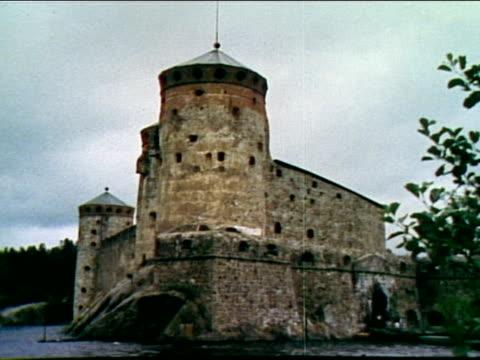 finnish men riding sliding bridge across water toward castle; motor boat passing by castle; savonlinna opera fest at olavinlinna castle. - 堀点の映像素材/bロール