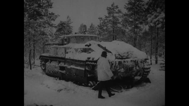 MS Finnish soldier next to snowcovered abandoned Soviet tank / VS frozen bodies of Russian soldiers lying in snow next to tank / Note exact day not...