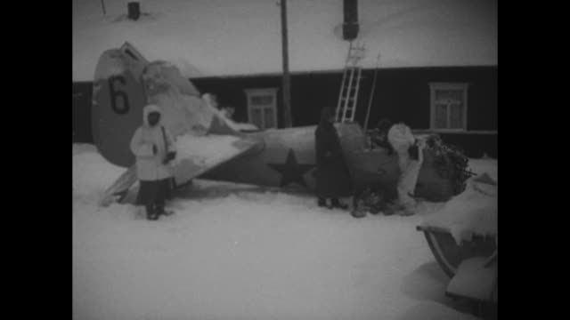 VS Finnish soldiers examine the wrecked engine propeller and fuselage of a downed Russian warplane / Men firing antiaircraft guns POV through the...