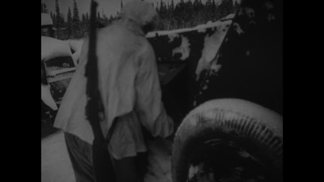 VS Finnish soldiers look thru abandoned Soviet armored vehicles along snowcovered road / MS Finnish soldiers with hands on gun protruding from...