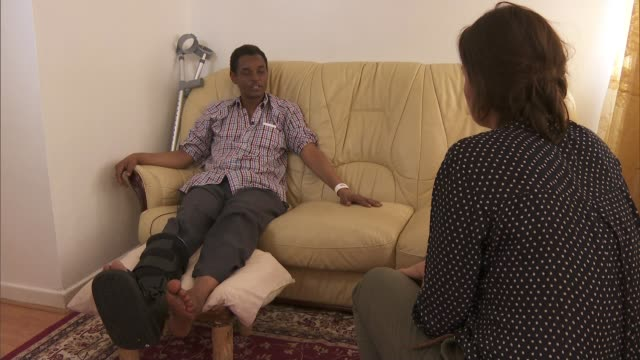 man injured in attack interviewed int yassin hersi i interview sot it was chaos hersi with with broken leg on sofa hersi interview sot old man... - broken leg stock videos & royalty-free footage