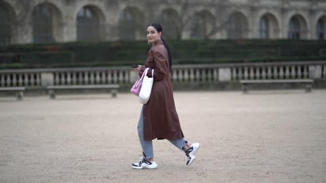 vídeos de stock e filmes b-roll de fiona zanetti wears a brown leather coat, a pink bag, sneakers, outside kenzo, during paris fashion week - menswear f/w 2019-2020, on january 20,... - ténis calçado desportivo