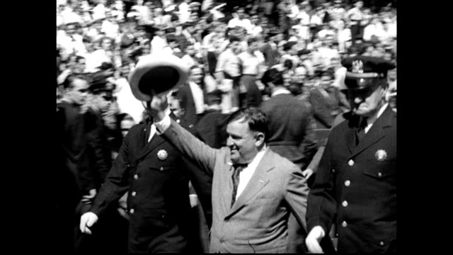 Fiorello LaGuardia marching in parade w/ NYC police operating steam shovel riding boat w/ officers sitting at desk at podium climbing ladder in...