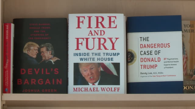 wgn 'fire and fury inside the trump white house' book on display with other trumprelated books on a bookshelf in a bookstore in chicago on jan 9 2017 - book shop stock videos & royalty-free footage