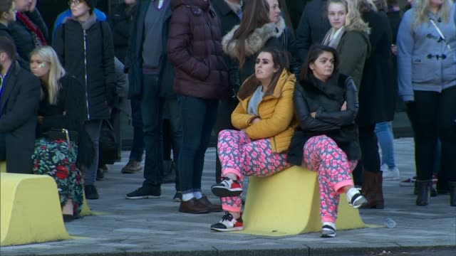 Hundreds of vehicles destroyed ENGLAND Liverpool EXT Women sitting on concrete bollard as people standing on street during evacuation People outside...