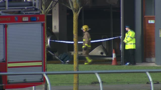Hundreds of vehicles destroyed ENGLAND Liverpool Liverpool Echo Arena EXT Firefighters along Burnt out cars TILT UP remains of multi story car park...