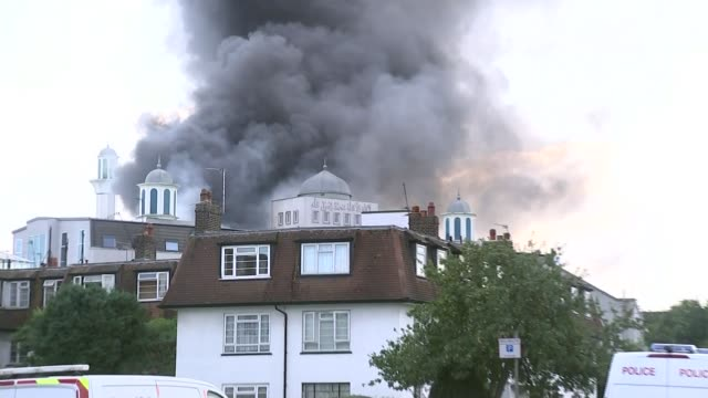 fire at the baitul futuh mosque in morden england london morden ext smoke rising from baitul futuh mosque pull out police vehicles and police cordon... - ロープ仕切り点の映像素材/bロール