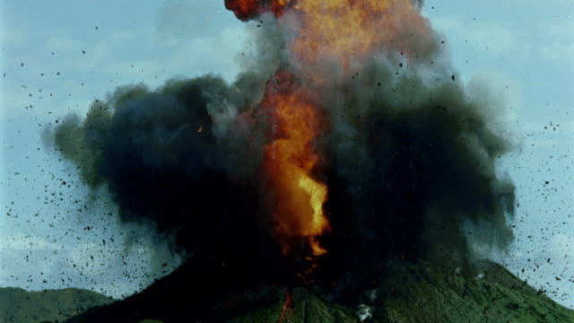 fire + black smoke from erupting volcano / tilt up to smoke - cenere video stock e b–roll