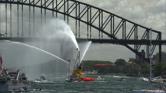 WS Fire boat spraying water in front of Sydney Harbor Bridge, Sydney, New South Wales, Australia