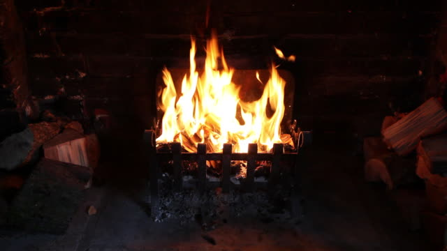 fire burning in grate in inglenook fireplace - 暖炉点の映像素材/bロール