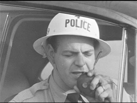 vídeos de stock e filmes b-roll de fire burning on grass near swing set. policeman in hardhat calling on radio. ops center: passing on word about school fire, calling firemen. 1950s... - anticomunismo