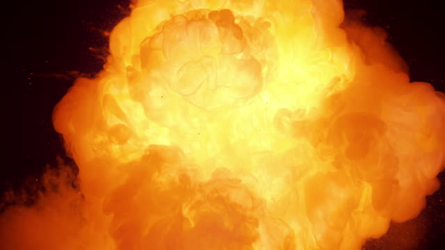 slo mo fire cloud bursting from black background - fuoco video stock e b–roll