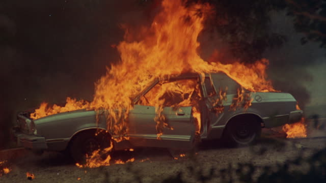 Fire consumes a sedan styled car.