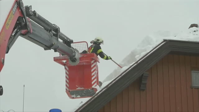 Fire crews clearing snow off rooves of houses after heavy snowfall in Annaberg in the Austrian Alps