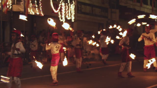 stockvideo's en b-roll-footage met ms pan slo mo fire dancers playing with fire in esala perahera festival at night / kandy, sri lanka - sri lankaanse cultuur