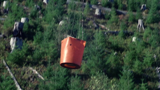 MS TS Fire department helicopter with water dropping bucket hanging below and dips bucket into small lake