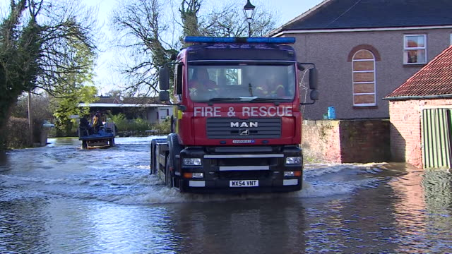 fire engine driving through flooded village of fishlake in doncaster - village stock videos & royalty-free footage