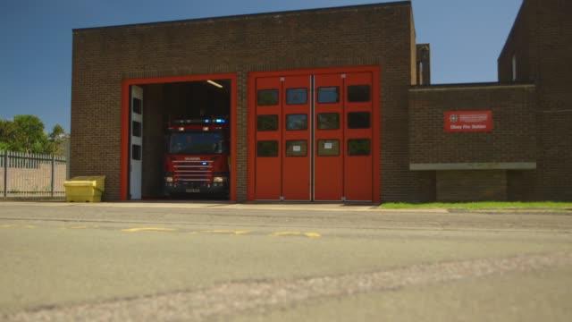 vídeos y material grabado en eventos de stock de fire engine leaving the fire station with lights flashing - parque de bomberos