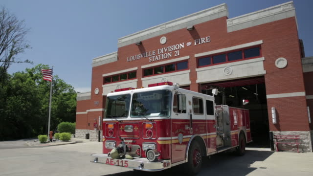 fire engine sitting outside fire house - feuerwache stock-videos und b-roll-filmmaterial