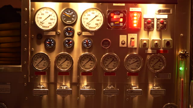 Fire engine truck gauges at night in a neighborhood.