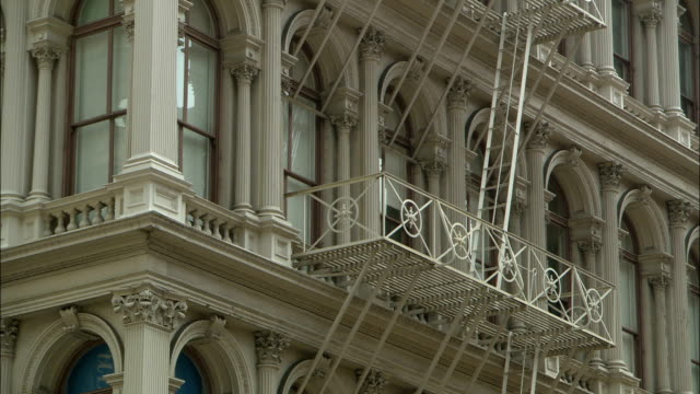 a fire escape conceals ornate columns and arches on a high-rise facade. - fire escape stock videos & royalty-free footage