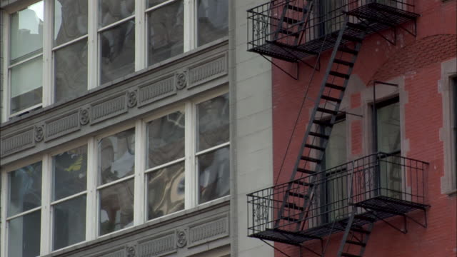 a fire escape hangs on the outside of a red building on 5th avenue in manhattan. - fire escape stock videos & royalty-free footage