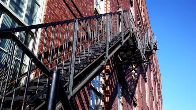 fire escape on red brick building facade - fire escape stock videos & royalty-free footage