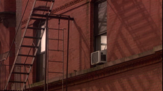 a fire escape zigzags up the side of a brick apartment building. - 非常階段点の映像素材/bロール