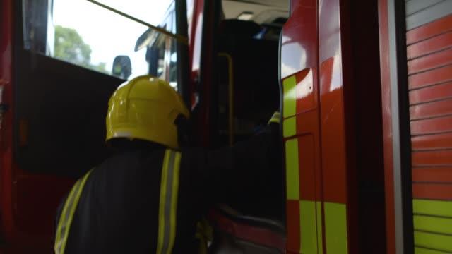 vídeos y material grabado en eventos de stock de fire fighter climbs into fire engine - parque de bomberos