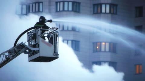 stockvideo's en b-roll-footage met fire fighter during intense fire extinguishment - reddingswerker