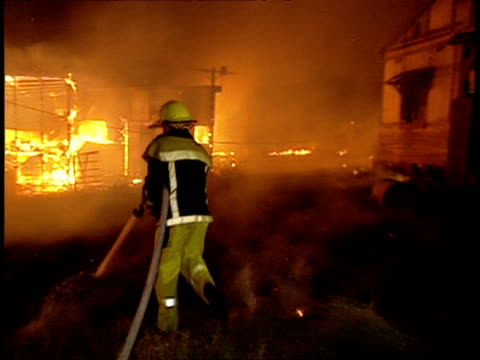 vidéos et rushes de ms fire fighter hosing down burning shell of house at night - destruction