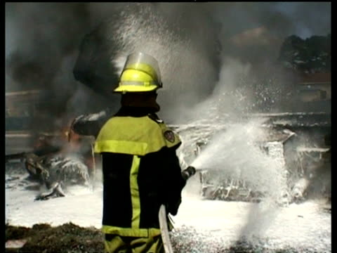 mcu fire fighter hosing down burning tanker truck with foam - extinguishing stock videos and b-roll footage