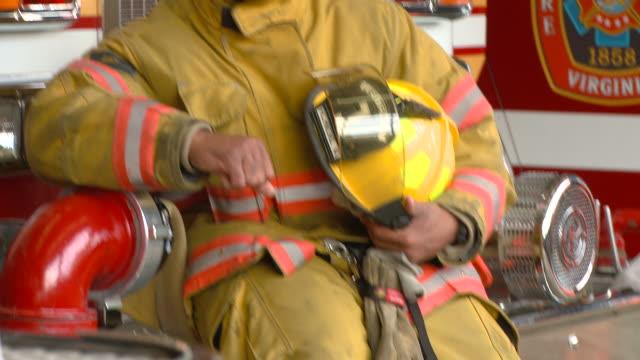 vídeos y material grabado en eventos de stock de ms tu portrait fire fighter sitting on fire engine/ richmond, virginia - parque de bomberos