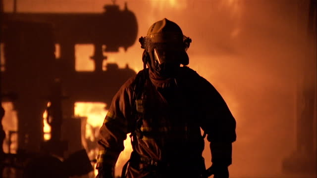 A fire fighter walks towards the camera in full protective gear.