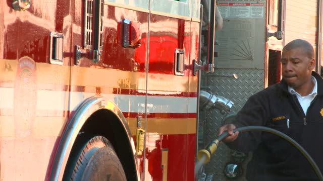 ms pan fire fighter washing fire truck with hose/ richmond, virginia - fighter stock videos and b-roll footage