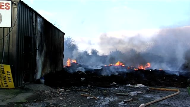 fire fighters are continuing to investigate the circumstances surrounding a blaze which destroyed thousands of tyres at a scrap yard outside... - umgeben stock-videos und b-roll-filmmaterial