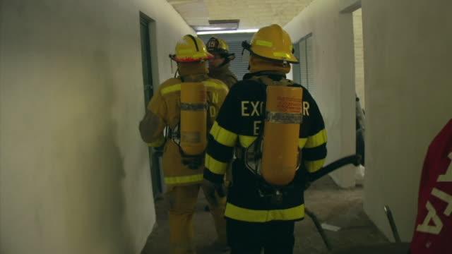 ms pov fire fighters practicing going into room with fire, ecuador - tre fjärdedels längd bildbanksvideor och videomaterial från bakom kulisserna